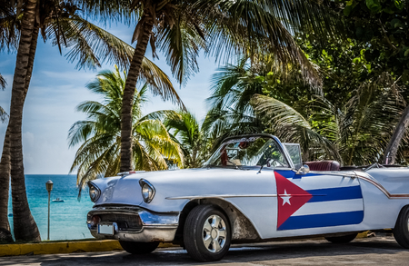 American white cabriolet vintage car with cuban flag on the side door parked under palms near the beach - Cuba Series Report