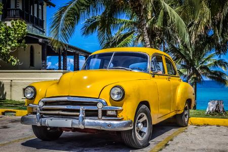 varadero: Gelber amerikanischer Chevrolet Oldtimer parkt unter Palmen am Strand in Varadero Kuba - Serie Kuba Reportage