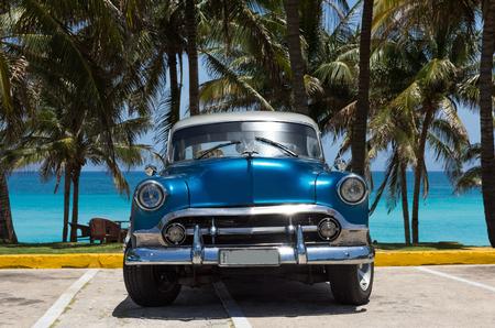 Amerykański niebieski klasyczny samochód ze srebrnym dachem zaparkowany pod palmami w Varadero na Kubie - Series Cuba Reportage