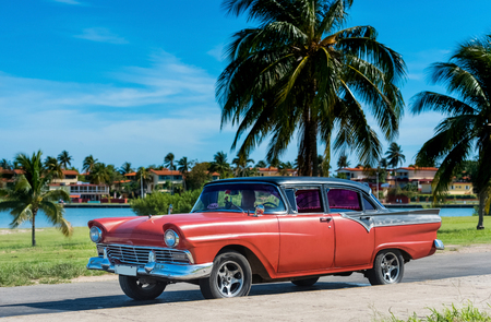American red classic car parked under blue sky near the beach in Havana Cuba - Series Cuba Reportage