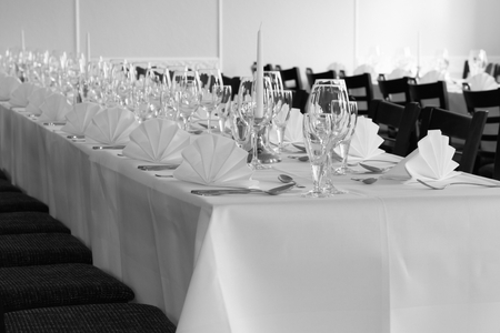 Black and white - Festive table arrangement with glasses and served and cutlery Фото со стока