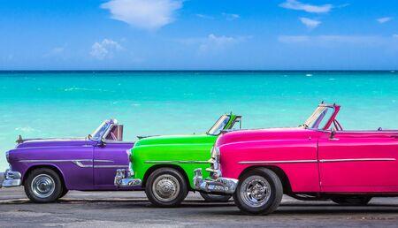 Trois voitures anciennes convertibles américaines garées sur la plage de Cuba - série Cuba Reportage