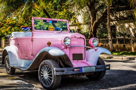 Klasyczny kabriolet w stylu amerykańskiej róży zaparkowany pod palmami w Varadero na Kubie - Series Cuba Reportage