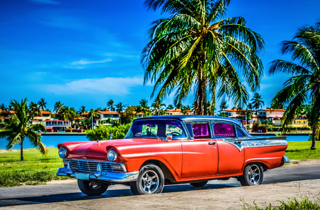 American red classic car parked under blue skies near the beach in Havana Cuba - Series Cuba Reportage 報道画像