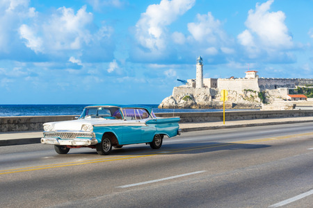 American blue white 1959 vintage car on the promenade Malecon and in the background the Castillo de los Tres Reyes del Morro in Havana City Cuba - series Cuba Reportage