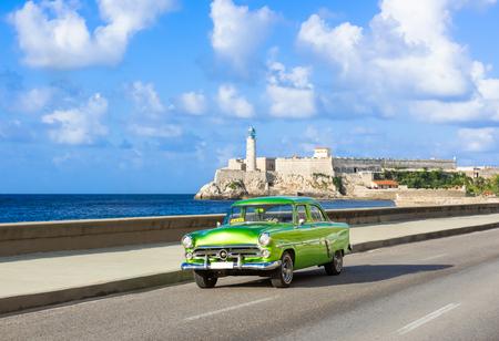 American green 1952 vintage car on the promenade Malecon and in the background the Castillo de los Tres Reyes del Morro in Havana City Cuba - series Cuba Reportage Redactioneel
