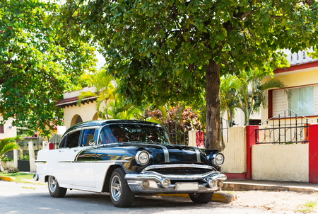 American black white 1956 vintage car parked in the sidestreet before a house in Varadero Cuba - Serie Cuba Reportage Redactioneel
