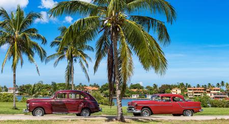 American red brown vintage cars parked under blue skies near the beach in Havana Cuba - Series Cuba Reportage Redactioneel