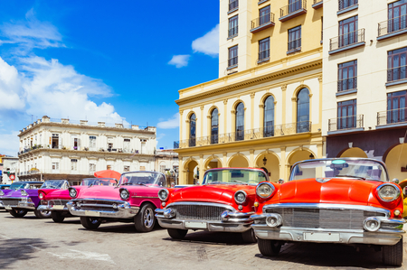 American red 1955, 1956 convertible, 1957 convertible and 1958 convertible vintage car parked in row in the old town from Havana City Cuba - Series Cuba Reportage
