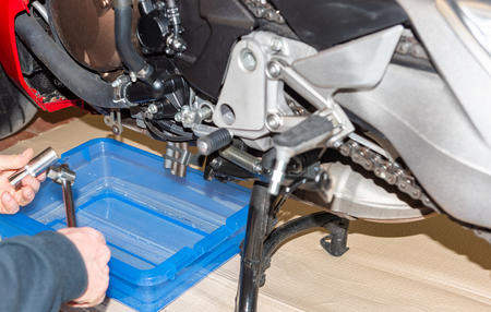 Motorbike in the a service station with oil Change - Serie repair workshop 版權商用圖片