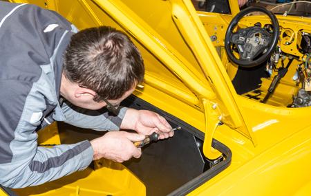 Mecánico de automóviles vuelve a atornillar las piezas del automóvil después de la restauración - Serie Repair Workshop Foto de archivo