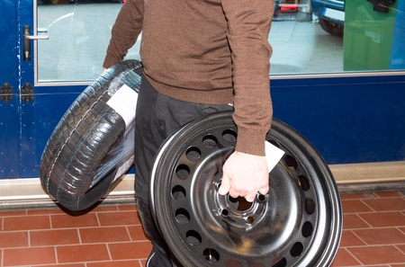 Car mechanic carries the wheels and changes the car tires - Serie Repair Workshop