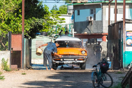 A cuban man washing an american brown 1955 Desoto classic car with white roof in a car wash area in Quemado de guines Cuba - Serie Cuba Reportage