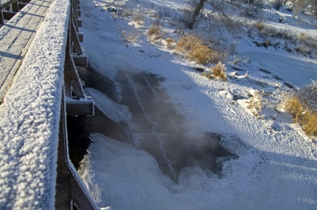 Steam rising above the frozen river at the dam photo