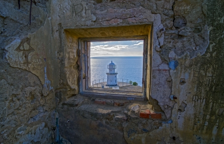 View of the new lighthouse from the window of a ruined building an old lighthouse  photo