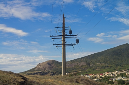 Power line pylon against a blue sky in the mountains  photo