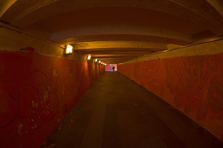Lonely silhouette in a long underground passage with red walls  photo