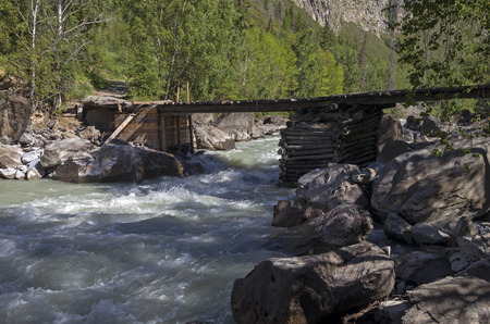 Old dilapidated bridge on the mountain river. Altai, Russia photo