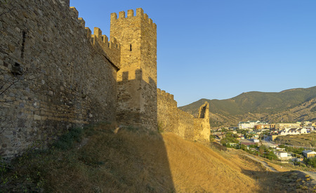 Genoese fortress in Sudak, Crimea. Early morning. The shadow of the tower on the fortress wall.