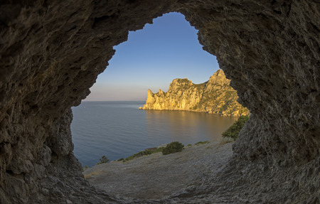 View of the coastal cliffs from a small grotto in the rock. Early quiet cloudless morning. Crimea. Stock Photo