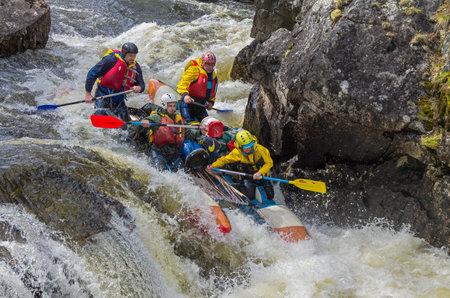 narrowly: VUOSNAYOKI RIVER MURMANSK REGION RUSSIA JUNE September 2015: Sport catamaran overcomes a difficult rarids on Vuosnayoki river the border of the Murmansk region and Karelia Russia. Editorial
