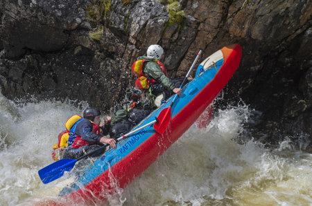 narrowly: VUOSNAYOKI RIVER MURMANSK REGION RUSSIA JUNE September 2015: Sport catamaran in hard and dangerous situation when overcoming a difficult rapids on Vuosnayoki river the border of the Murmansk region and Karelia Russia.
