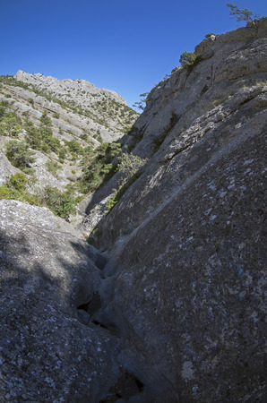 narrowly: The narrow rocky gorge in the Crimean mountains. Riverbed pierced in the stone by rain and melt water. Stock Photo