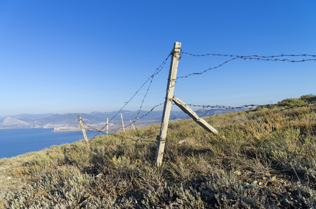 rickety: Fence of the abandoned military base on the top of the mountain above the sea. Meganom cape, Crimea. Stock Photo