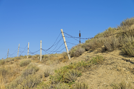 rickety: Leaky rickety fence on the site of the disbanded military base. Meganom cape, Crimea. Stock Photo
