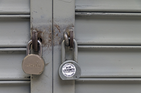 jalousie: NEW YORK CITY, USA - AUGUST 23, 2015: Two padlocks on the closed iron shutters