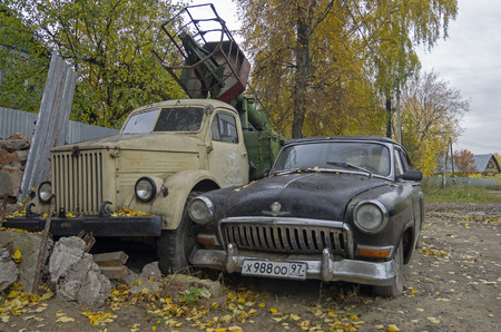 51: KUPAVNA, RUSSIA - OCTOBER 9, 2011: Old Russian cars Volga GAZ 21 and truck GAZ 51 on the street of the Kupavna village in Moscow suburbs. Waiting for renovation by some homebrew enthusiast Editorial