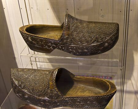 traditionary: Pair of traditional Dutch wooden shoes klomps decorated with carvings in a showcase in the tourist village of Zaanse Schans near Amsterdam.