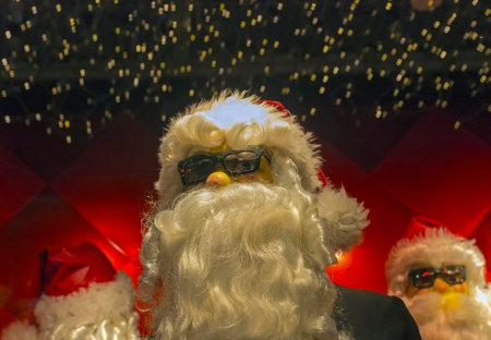 pere noel: PARIS, FRANCE - DECEMBER 17, 2013: Showcases of Paris department stores. Cool figures of Santa Claus in sunglasses. Editorial