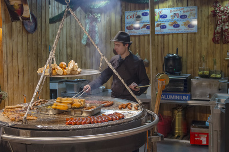 traditionary: PARIS, FRANCE - December 21, 2012: Cooking traditional food a sandwich with a grilled sausage at a Christmas fair in Paris.