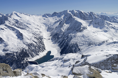 energetics: The dam and the artificial lake in a mountain gorge. View from the top of the Hintertux glacier in the Austrian Alps. Height - 3250 meters above sea level. Such small reservoirs used to supply hydroelectric power stations in ithe surrounding valleys