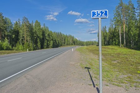 milepost: Milepost on the federal highway A121. Sunny day in June. South Karelia, Russia.
