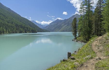 The trail runs along the shore of the Kucherla lake. Altai Mountains, Russia. Sunny summer day.
