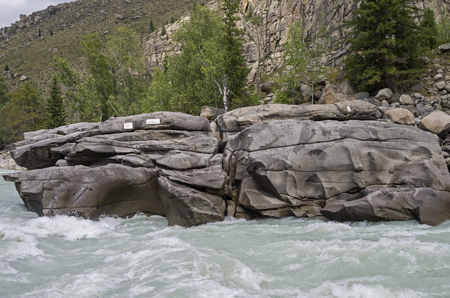 atlantes: Stone at the end of a rapids with with plaque in memory of dead tourists. Rapids Atlantes on Argut river. Altai Mountains, Russia. Stock Photo