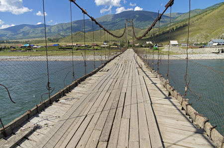 Old suspension bridge over the river Katun in the village Tungur. Altai,  Russia. Sunny summer day.