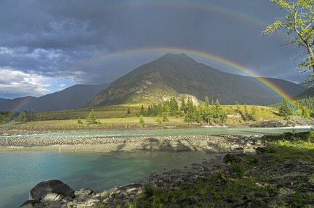 Rainbow over the river. Argut River merger with Katun. Altai Mountains, Russia. August.