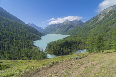 The hiking trail on the hillside leading to the Kucherla lake. Altai Mountains, Russia. Sunny summer day. Stock Photo