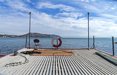 sudak: A funny situation on a pier: an old chair on the old carpet with sea views. Sudak bay. Crimea.
