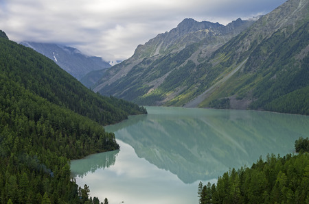 Reflection of mountains in the lake. Kucherla lake. Altai Mountains, Russia. Overcast summer morning.