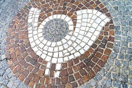 posthorn: MAYRHOFEN, AUSTRIA - MARCH 10, 2017: The emblem of The emblem of a post office (post horn) in the form of a mosaic on the sidewalk. Austria, Tyrol, Mayrhofen. Editorial