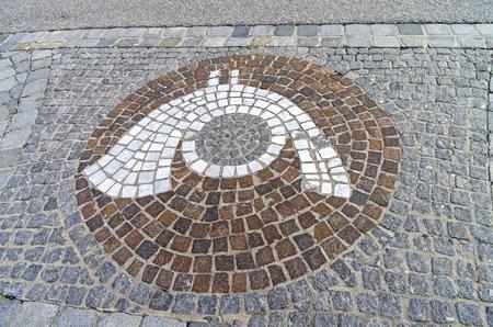 posthorn: MAYRHOFEN, AUSTRIA - MARCH 10, 2017: The emblem of The emblem of a post office (post horn) in the form of a mosaic on the sidewalk. Austria, Tyrol, Mayrhofen. Stock Photo