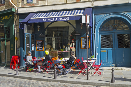 ile de la cite: PARIS, FRANCE - APRIL 2, 2017: Tables on the sidewalk in front of a small cafe. The island of Cite, a sunny day in early April. Paris, France.