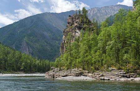 The Oka Sayanskaya River in the Orkho-Bom gorge. A rock before the rapids Okinski. Sunny summer day. Buryatia, Siberia, Russia.
