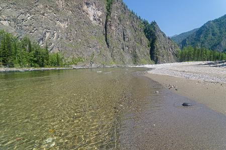 The Oka Sayanskaya River in the Orkho-Bom gorge. A small sandy beach. Sunny summer day. Buryatia, Siberia, Russia.