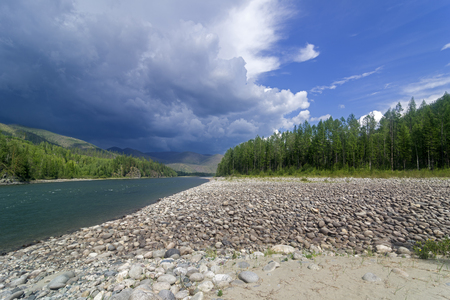A storm cloud over the river. Oka Sayanskaya river at the end of the gorge Orkho-Bom, Eastern Sayan, Siberia, Russia. The beginning of August. Stock Photo