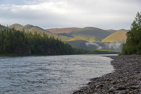 Low clouds on a mountain slope. Oka Sayanskaya river at the end of the gorge Orkho-Bom,  Eastern Sayan, Siberia, Russia. Cloudy day in early August.